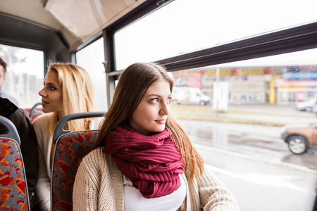 buss: Beautiful young women traveling by bus, looking out of window, having fun in town. Stock Photo
