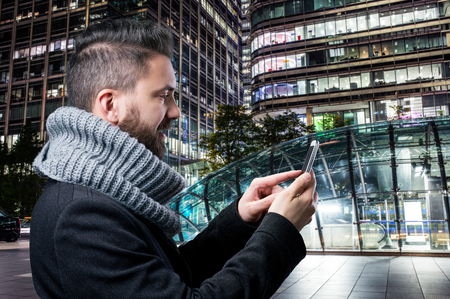 touch screen: Young handsome man with smart phone in illuminated night London city