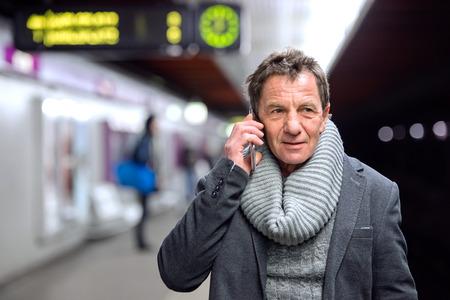 waiting phone call: Beautiful senior man standing at the underground platform, waiting, talking on the phone