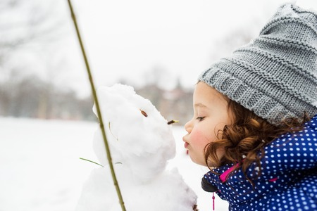 kissing mouth: Beautiful little girl kissing a snowman, playing outside in winter nature