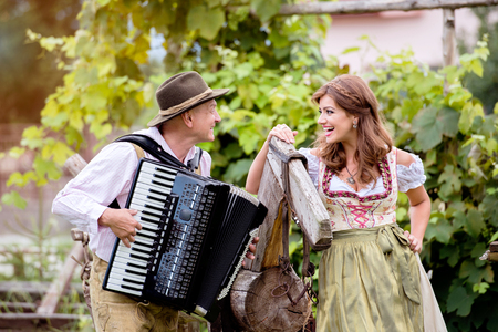 green clothes: Couple in traditional bavarian clothes standing by an old wooden horse in green garden, man playing accordion. Oktoberfest.