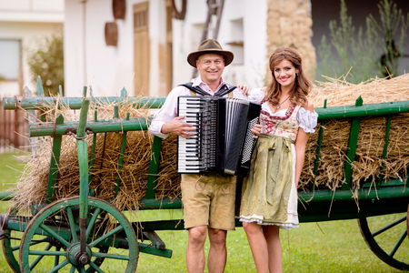traditional costume: Couple in traditional bavarian clothes standing in front of wooden cart with dried hay. Man playing accordion. Oktoberfest. Stock Photo