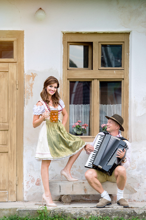 dirndl dress: Couple in traditional bavarian clothes standing against old country house, man playing accordion, woman holding a mug of beer. Oktoberfest.