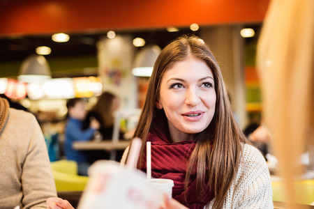 fast food restaurant: Beautiful young woman eating out in fast food restaurant, talking, having fun with friends Stock Photo