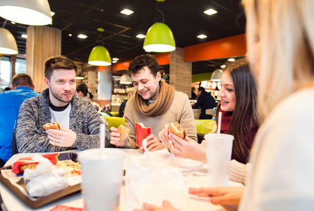 out of town: Group of young people eating out and talking, having fun in town Stock Photo