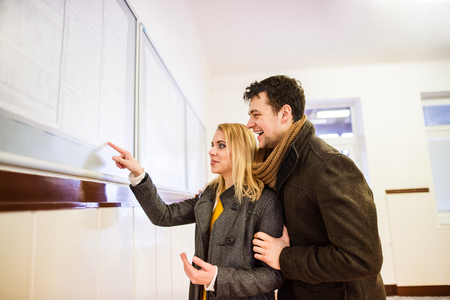buss: Beautiful young couple traveling, looking at timetable in bus waiting room, having fun together. Stock Photo