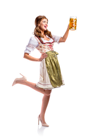 vest in isolated: Beautiful young woman in traditional bavarian dress holding a mug of beer. Oktoberfest. Studio shot on white background, isolated. Stock Photo