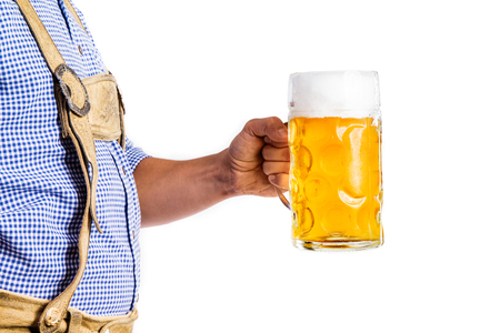 lederhosen: Unrecognizable young man in traditional bavarian clothes holding a mug of beer. Oktoberfest. Studio shot on white background, isolated.