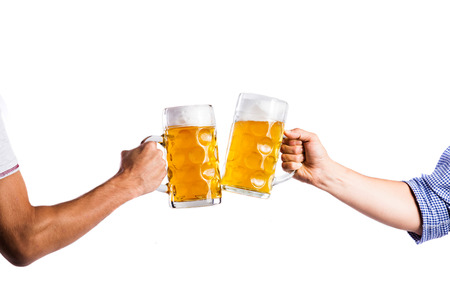 clinking: Hands of two unrecognizable men clinking with beer mugs. Oktoberfest. Studio shot on white background, isolated.