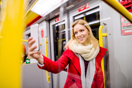cool gadget: Beautiful young blond woman in red coat in subway train, holding a smart phone, taking selfie
