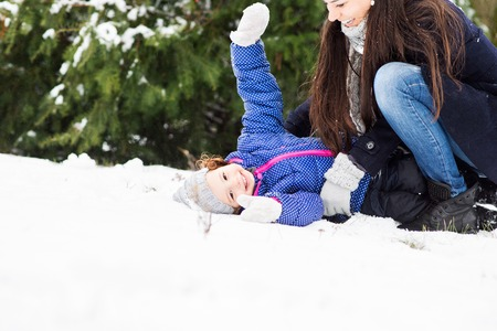 family outside: Beautiful young mother with her cute little daughter playing outside in winter nature, girl lying in the snow Stock Photo