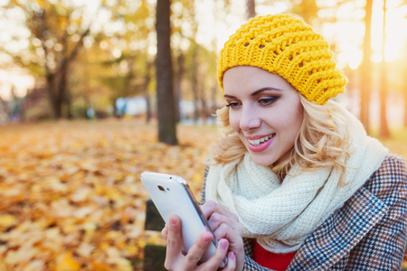 Beautiful young woman in yellow knitted hat, white scarf and checked coat holding smart phone, texting. Sunny autumn park. Stock Photo