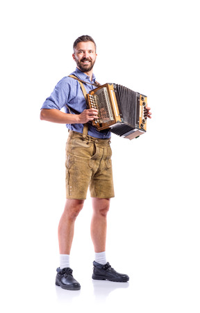 Handsome young man in traditional bavarian clothes playing accordion. Oktoberfest. Studio shot on white background, isolated. Stockfoto
