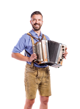 Handsome young man in traditional bavarian clothes playing accordion. Oktoberfest. Studio shot on white background, isolated. 版權商用圖片