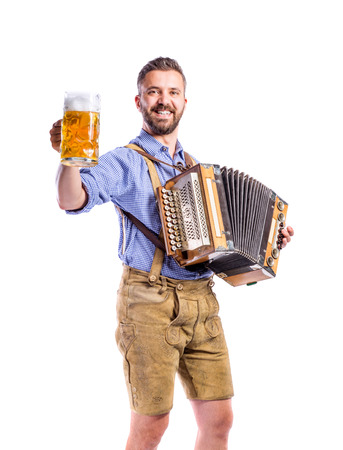 Handsome young man in traditional bavarian clothes holding a mug of beer, playing accordion. Oktoberfest. Studio shot on white background, isolated.
