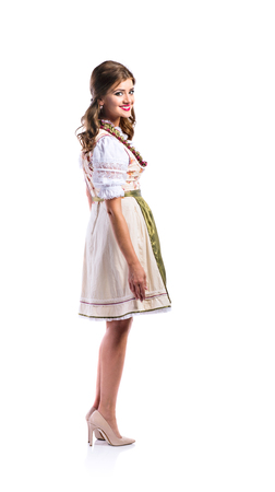 view woman: Beautiful young woman in traditional bavarian dress standing. Oktoberfest. Studio shot on white background, isolated.