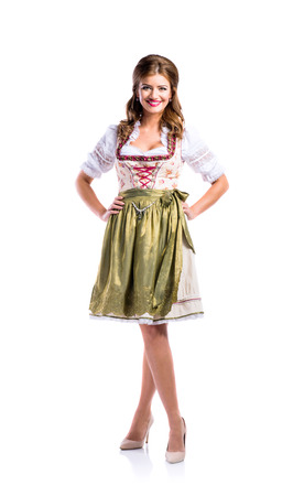 dirndl: Beautiful young woman in traditional bavarian dress standing, hands on hips. Oktoberfest. Studio shot on white background, isolated.