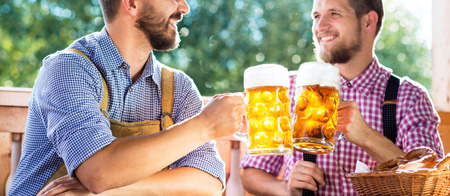 Two handsome hipster young men in traditional bavarian clothes holding mugs of beer, clinking. Oktoberfest. Sunny summer garden. Stock Photo