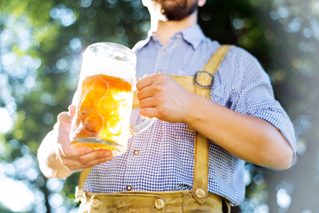 lederhosen: Unrecognizable young hipster man in traditional bavarian clothes holding a mug of beer. Oktoberfest. Sunny summer garden.