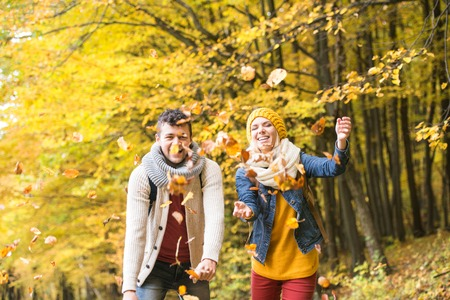 walk in: Beautiful couple on a walk in colorful autumn forest throwing leaves up in the air, smiling