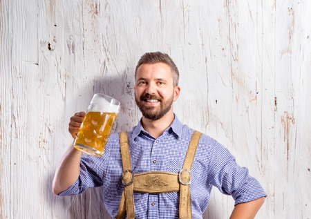 summer festival: Handsome young man in traditional bavarian clothes holding a mug of beer. Oktoberfest. Studio shot on white wooden background. Stock Photo