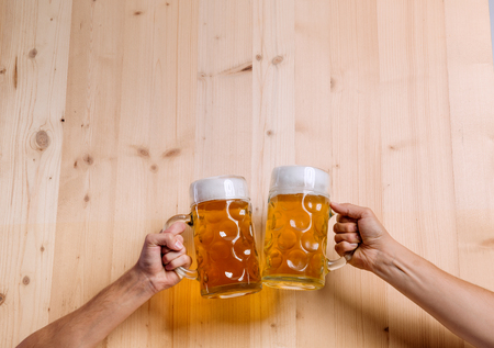 clinking: Hands of two unrecognizable men clinking with beer mugs. Oktoberfest. Studio shot on brown wooden background. Copy space.