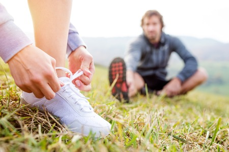 Beautiful couple running outside in autumn nature. Man stretching his legs, unrecognizable woman tying shoelaces