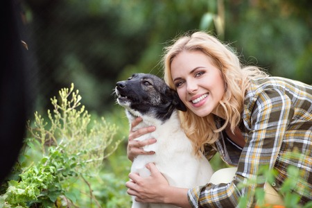mujer con perro: Beautiful blond woman with her dog in green garden