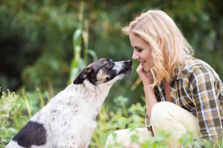 녹색 정원에서 그녀의 강아지와 함께 아름 다운 금발 여자 스톡 콘텐츠