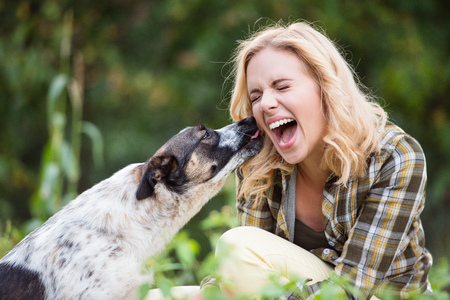 Beautiful blond woman with her dog in green garden