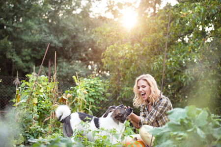 Beautiful blond woman with her dogs in green garden