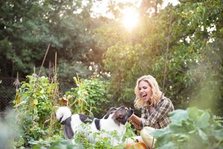 Schöne blonde Frau mit ihren Hunden im grünen Garten Standard-Bild - 64890916