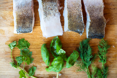 zander: Raw zander fish fillets with various herbs against a wooden cutting board. Stock Photo