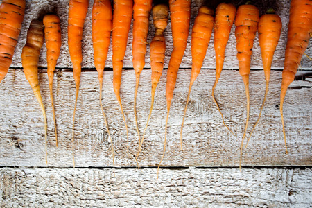carrot: Fresh carrot vegetable laid on white wooden table background in a row. Copy space. Flat lay.