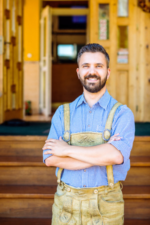 Handsome hipster young man in traditional bavarian clothes, arms crossed against old wooden rural house. Oktoberfest. Banco de Imagens