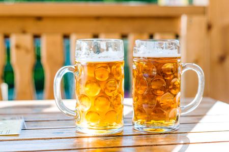 Zwei Becher Bier legte auf Holztisch, sonnigen Tag