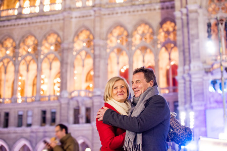 historical building: Senior couple in winter clothes on a walk in illuminated night city. Historical building. Vienna, Austria.