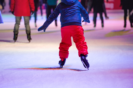 skating fun: Unrecognizable child ice skating at night in historical centre of the city of Vienna, Austria. Winter.