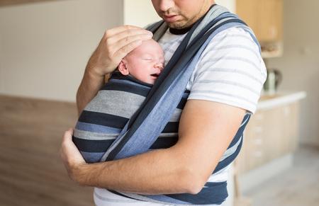 Close-up van onherkenbare jonge vader met zijn pasgeboren zoontje in slinger thuis