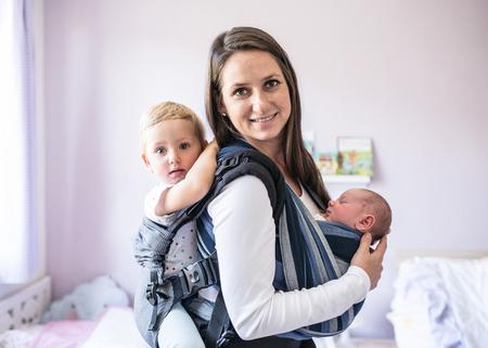 スリングに彼女の生まれたばかりの息子と自宅のベビー キャリアで彼女の娘の美しい若い母親