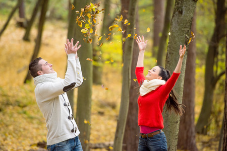 walk in: Beautiful young couple on a walk in autumn park throwing leaves