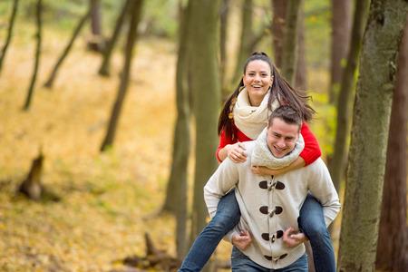 curare teneramente: Bella giovane coppia in amore, l'uomo dando la sua donna sulle spalle. Autunno foresta, giornata di sole. Archivio Fotografico
