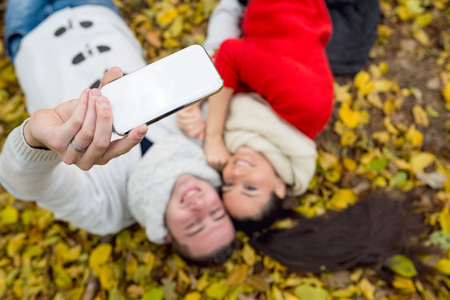 Beautiful young couple in autumn park lying on the ground covered with yellow leaves, taking selfie with smart phone