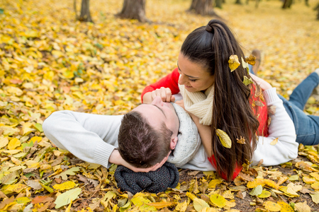 lying on leaves: Beautiful young couple in autumn park lying on the ground covered with yellow leaves Stock Photo