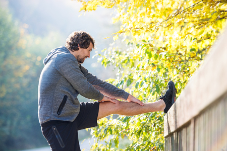 bridge in nature: Handsome young runner warming up and stretching his legs on a bridge. Sunny autumn nature.