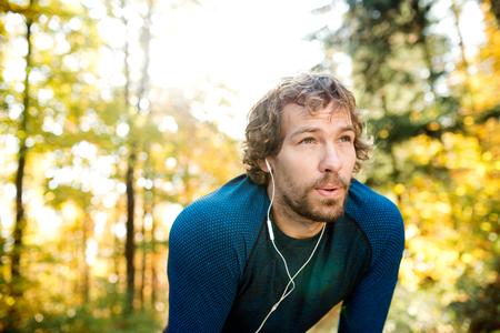 Jonge knappe loper met koptelefoon in zijn oren, muziek luisteren, buiten in zonnige herfst natuur, rusten, ademen uit