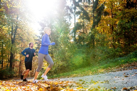 hombre deportista: Beautiful couple running together outside in sunny autumn forest