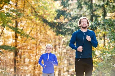 hombre deportista: Hermosa pareja corriendo juntos fuera de bosque soleado de otoño