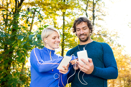 摘要: Beautiful couple running together outside in colorful sunny autumn forest using a fitness app on their smartphones. Using phone app for tracking weight loss progress, running goal or summary of their run. 版權商用圖片