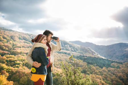 looking through: Beautiful young couple on a walk in sunny autumn forest, man looking through binoculars